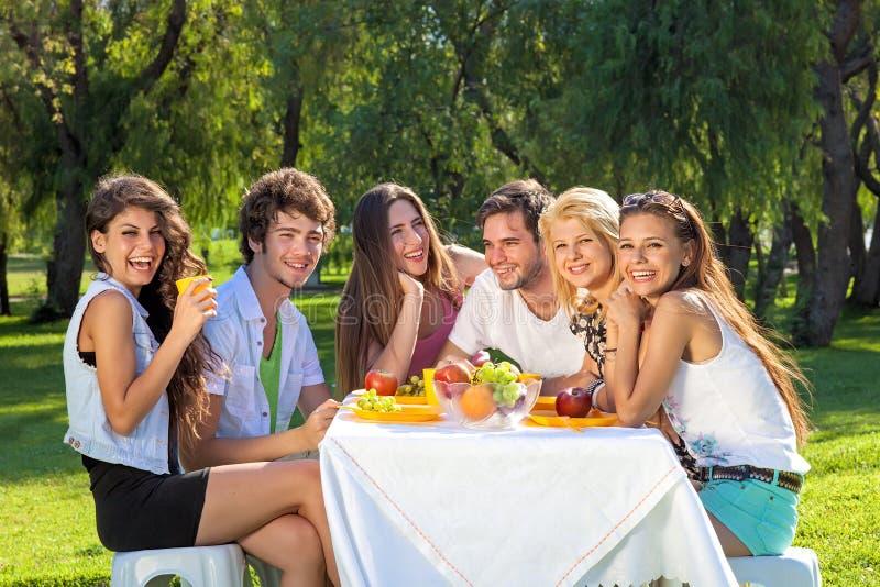 Os estudantes felizes completamente da vitalidade comem uma refeição frutado imagens de stock