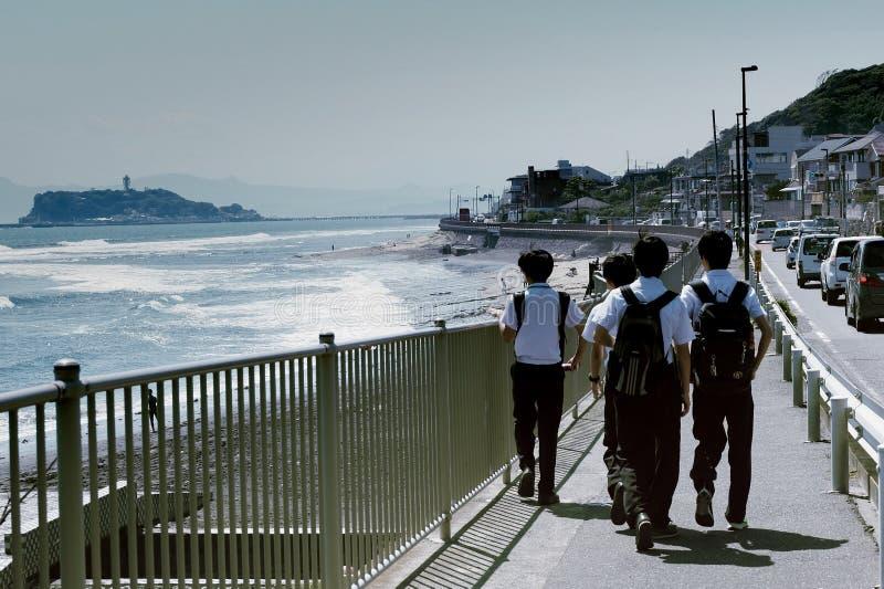 Os estudantes japoneses estão andando em casa na praia imagem de stock