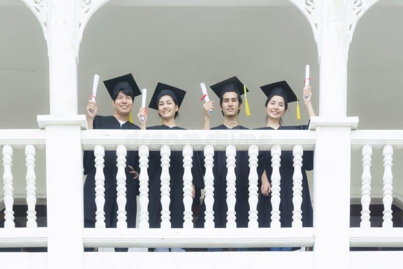 Os estudantes no sentimento felizes com vestidos da graduação estão no corrido fotografia de stock
