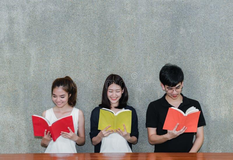 Os estudantes novos agrupam o livro de leitura do sorriso fotos de stock royalty free