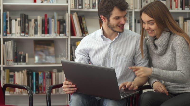Os estudantes olham algo no portátil na biblioteca imagem de stock
