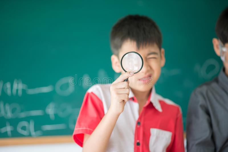 """Os estudantes pequenos tomam ciência do estudo ¿ de um glassï de ampliação do"""" na sala de aula imagem de stock"""