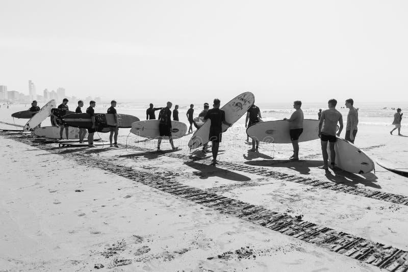 Os estudantes surfando das lições encalham o branco do preto do oceano fotografia de stock royalty free
