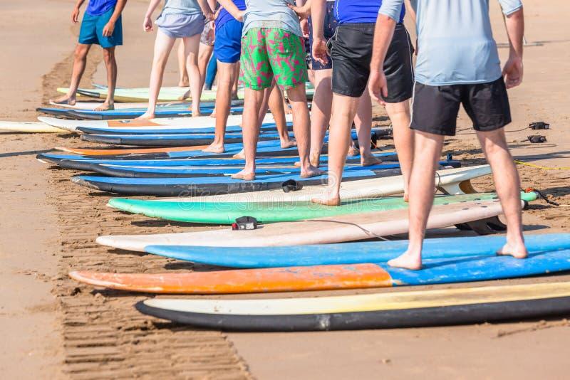 Os estudantes surfando das lições encalham o oceano foto de stock