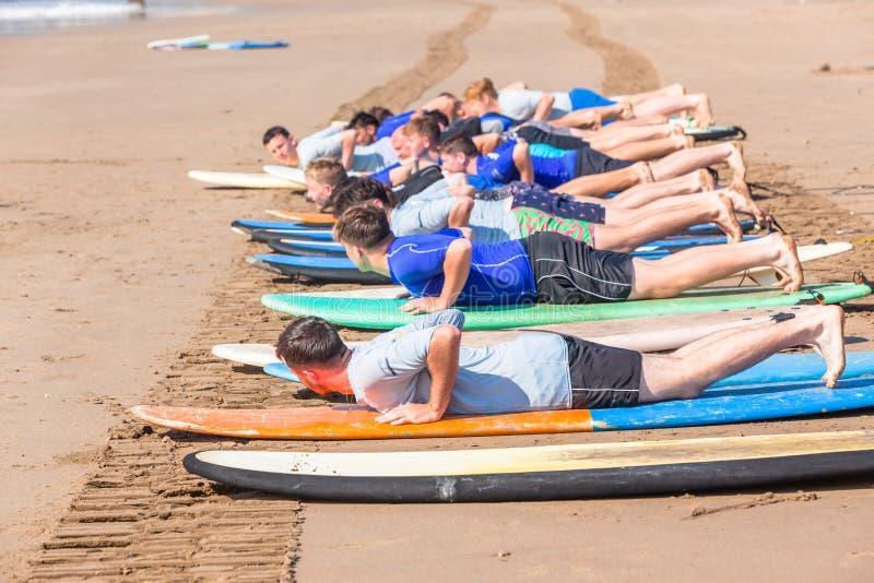 Os estudantes surfando das lições encalham o oceano fotografia de stock