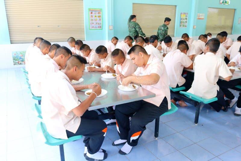 Os estudantes tailandeses no uniforme estão comendo o almoço junto no cantee imagem de stock royalty free