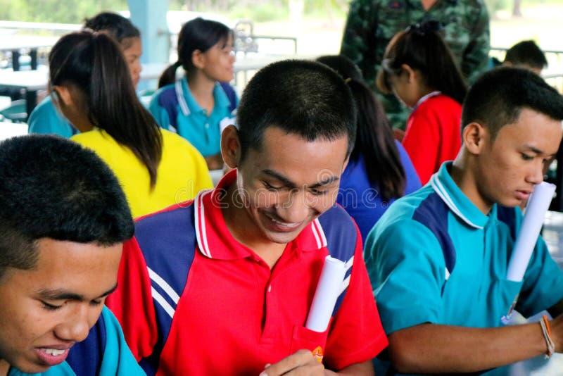 Os estudantes tailandeses no uniforme estão sentando-se junto no gym de Pakn imagem de stock royalty free