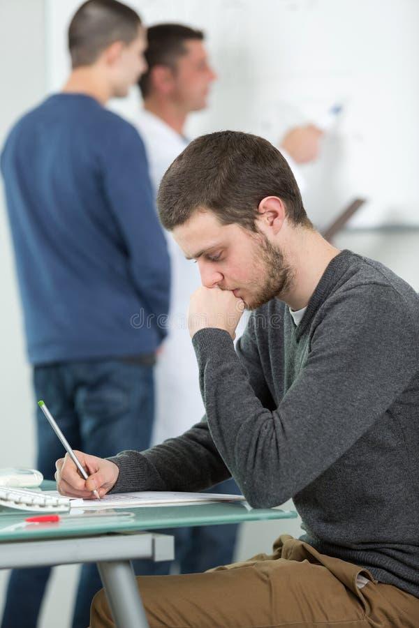 Os estudantes tomam notas na classe na High School imagem de stock