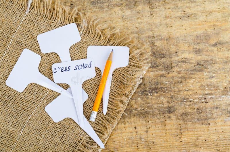 Os etiqueta-marcadores brancos para plantas encontram-se na serapilheira, no fundo de madeira imagem de stock royalty free
