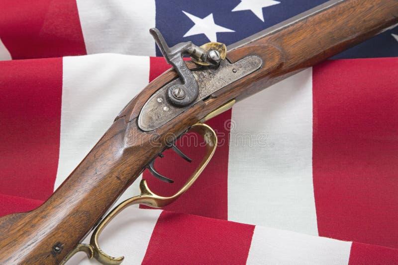 Os EUA embandeiram o rifle antigo revolucionário patriótico fotografia de stock