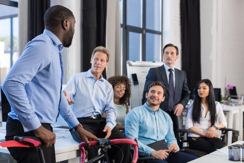 Os executivos agrupam no escritório criativo, homem de negócios afro-americano Hold Bicycle, Team Meeting And Communicating imagens de stock