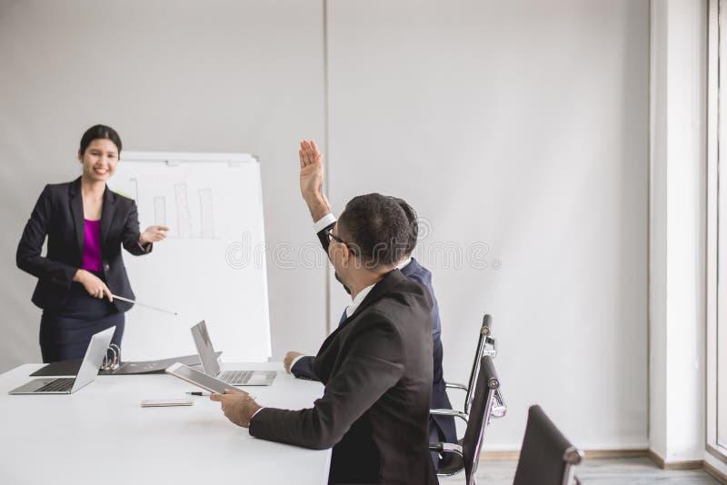 Os executivos asiáticos na reunião da sala de direção, grupo da equipe que discute com a mão aumentam acima junto na conferência  imagem de stock