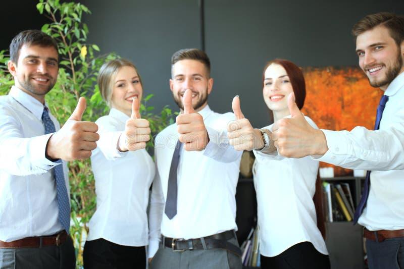Os executivos bem sucedidos com polegares levantam e sorrir fotos de stock