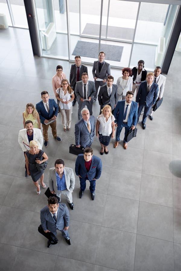 Os executivos bem sucedidos do retrato sorriem e olhando acima imagem de stock royalty free