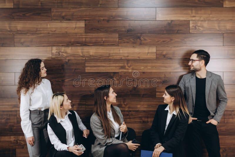 Os executivos bonitos estão usando o computador e estão sorrindo ao trabalhar no escritório foto de stock