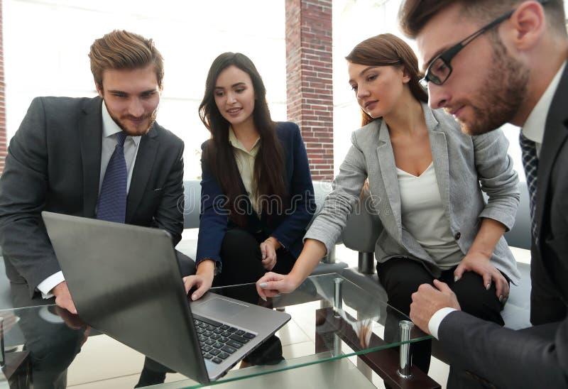 Os executivos concentrados usam um portátil durante uma conferência dentro foto de stock royalty free