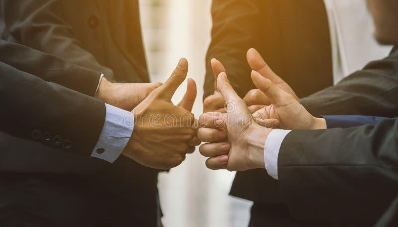 Os executivos do grupo de fatura das mãos dão os polegares acima dos trabalhos de equipa do sinal imagem de stock royalty free