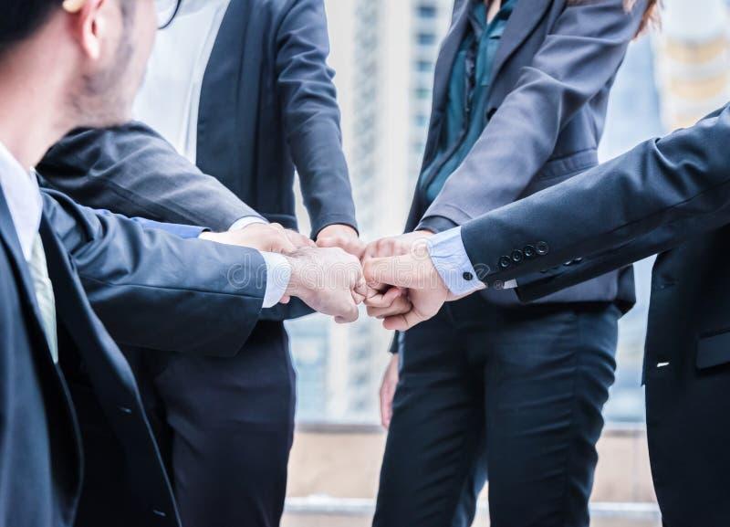 Os executivos do grupo de mãos que fazem o punho colidir trabalhos de equipa juntam-se ao conceito bem sucedido do apoio das mãos imagem de stock royalty free