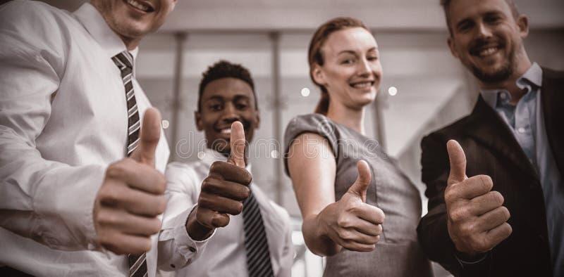Os executivos empresariais que mostram os polegares levantam o sinal imagens de stock