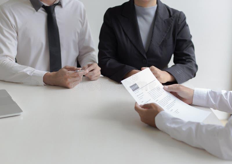 Os executivos estão entrevistando candidatos de trabalho e as comprovações de antecedentes preliminares, candidatos estão falando imagens de stock