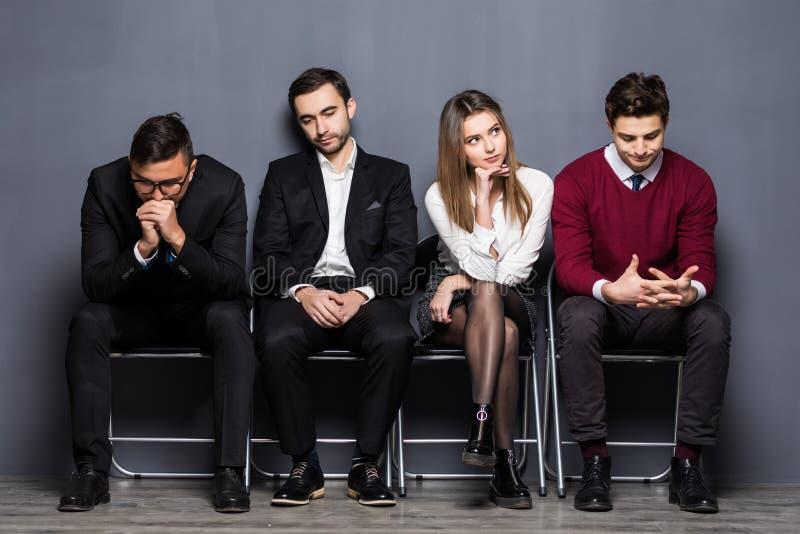 Os executivos estão obtendo furados ao sentar-se na cadeira Job Interview In Office de espera fotografia de stock