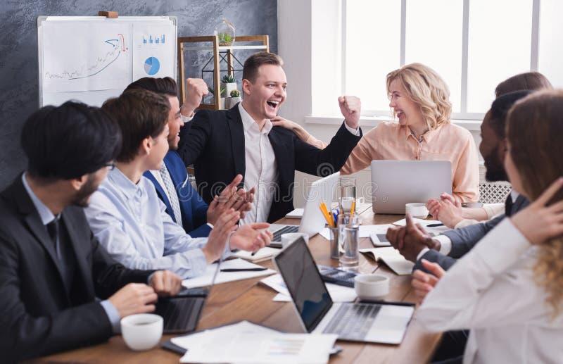 Os executivos felicitam o colega com seu sucesso imagens de stock royalty free
