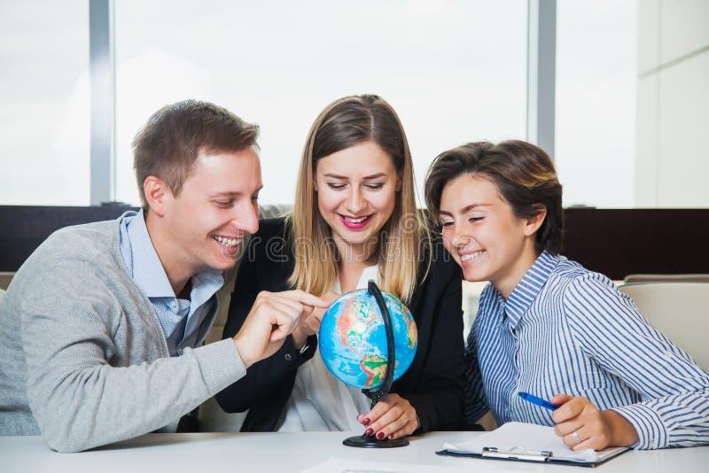 Os executivos guardam pouco globo do escritório e apontam nele imagens de stock