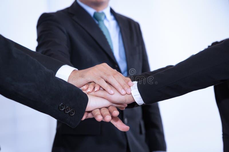 Os executivos juntam-se à mão da pilha ao reunir-se no escritório como a equipe imagem de stock