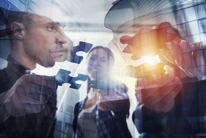 Os executivos juntam-se a partes do enigma Conceito dos trabalhos de equipa e da parceria Exposição dobro imagens de stock