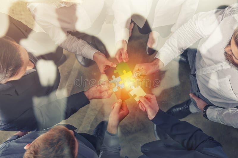 Os executivos juntam-se a partes do enigma Conceito dos trabalhos de equipa e da parceria Exposição dobro foto de stock royalty free