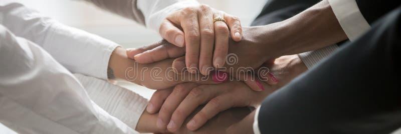 Os executivos multinacionais empilham seu símbolo das mãos junto da unidade foto de stock