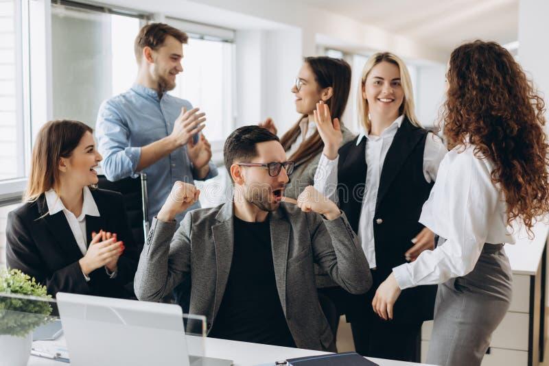 Os executivos novos bem sucedidos estão levantando as mãos nos punhos e estão gritando com felicidade ao trabalhar com um computa imagens de stock