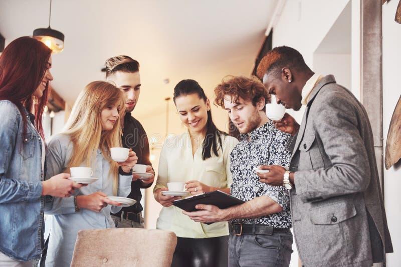 Os executivos novos bem sucedidos são de fala e de sorriso durante a ruptura de café no escritório fotos de stock