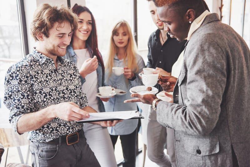 Os executivos novos bem sucedidos são de fala e de sorriso durante a ruptura de café no escritório fotografia de stock