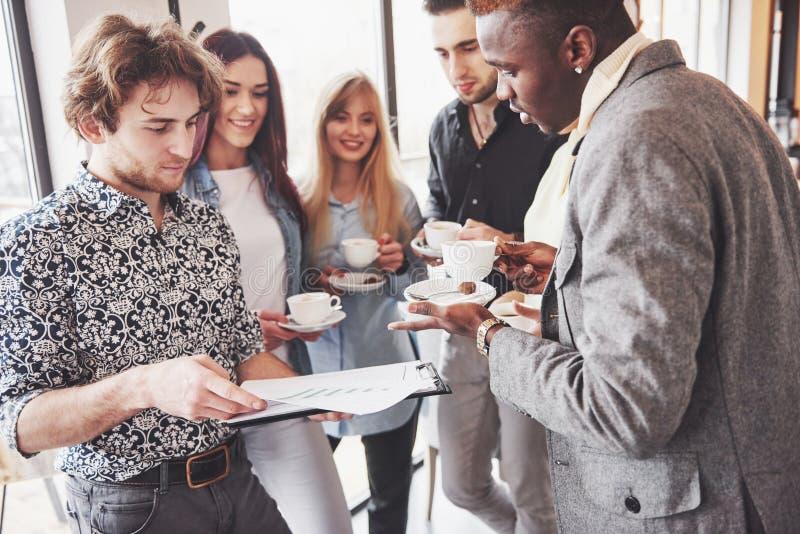 Os executivos novos bem sucedidos são de fala e de sorriso durante a ruptura de café no escritório imagem de stock