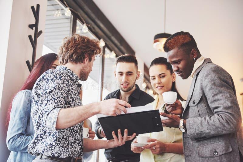 Os executivos novos bem sucedidos são de fala e de sorriso durante a ruptura de café no escritório fotos de stock royalty free