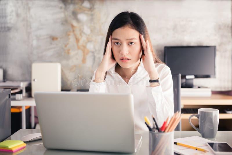 Os executivos novos estão sofrendo das dores de cabeça, mulheres asiáticas S imagens de stock