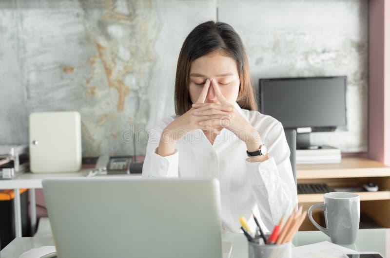 Os executivos novos estão sofrendo das dores de cabeça, mulheres asiáticas S imagem de stock royalty free