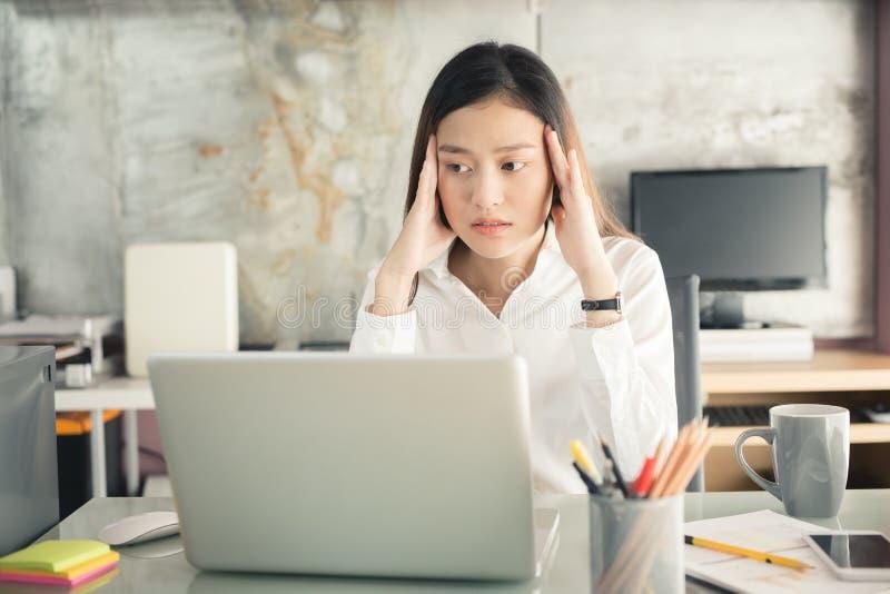 Os executivos novos estão sofrendo das dores de cabeça, mulheres asiáticas S imagem de stock