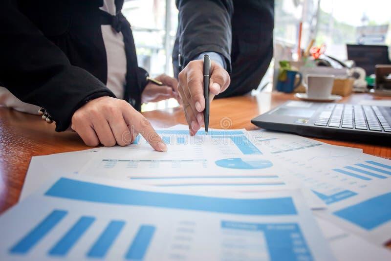 Os executivos que encontram a apresentação da ideia, analisam planos fotos de stock