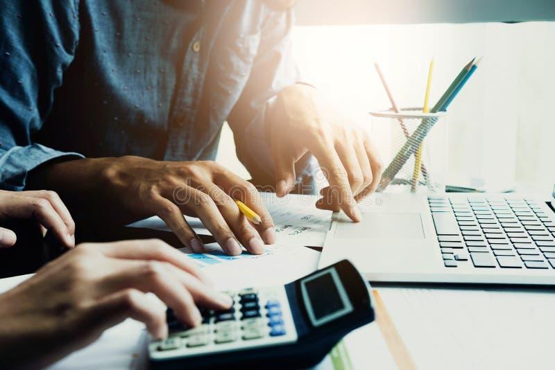 Os executivos que usam a calculadora e o laptop para discutem fotografia de stock