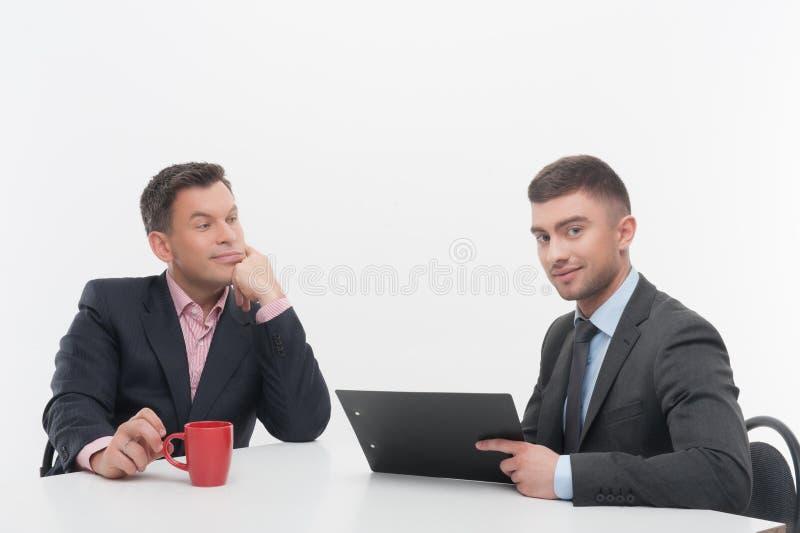 Os executivos superiores e júniors discutem fotos de stock