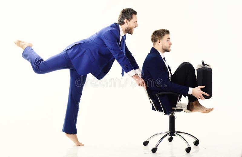 Os executivos têm o divertimento e montam-no na cadeira do escritório fotos de stock royalty free