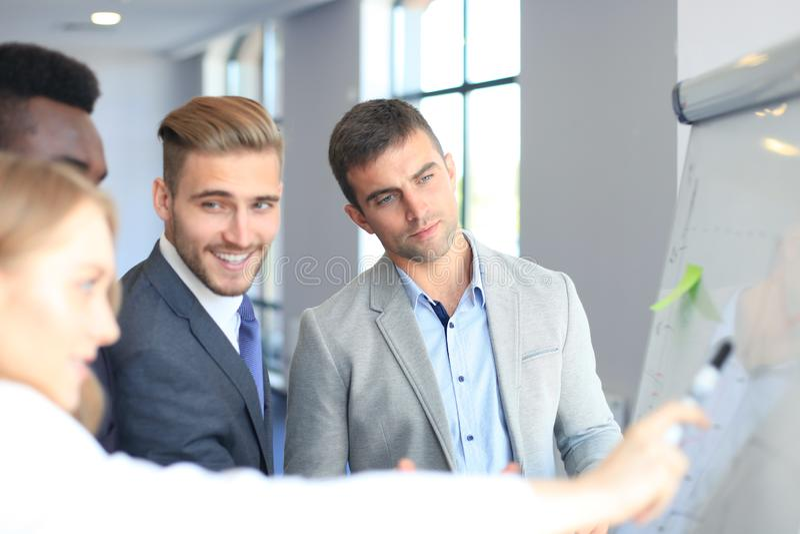 Os executivos team na apresentação que trabalha com cartas e diargams no flipchart imagem de stock