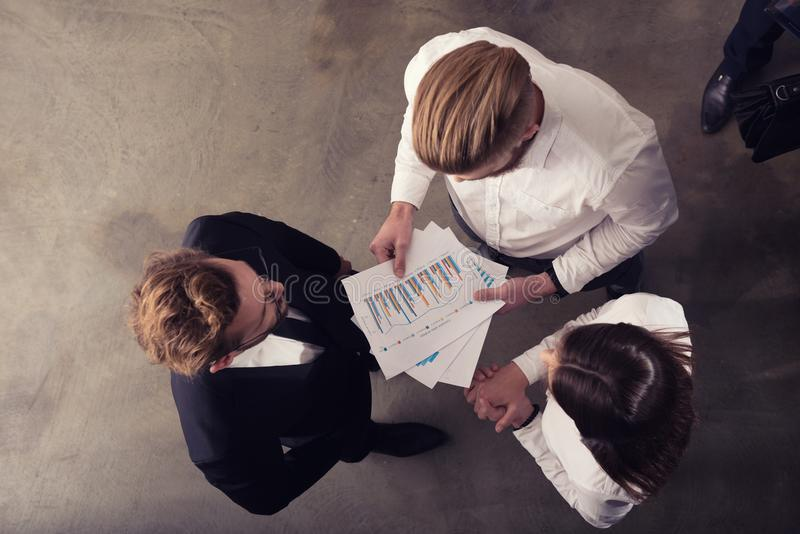 Os executivos trabalham com número das estatísticas da empresa imagem de stock