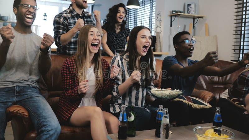 Os fãs de esportes afro-americanos comemoram a vitória em casa Jogo de observação do grito apaixonado dos suportes na tevê movime imagens de stock royalty free