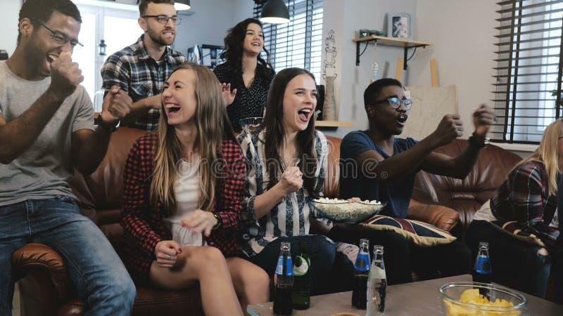 Os fãs de esportes afro-americanos comemoram a vitória em casa Jogo de observação do grito apaixonado dos suportes na tevê movime imagens de stock
