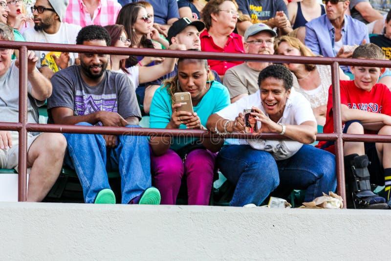 Os fãs entusiasmado saem de seus telefones celulares para tomar imagens imagens de stock