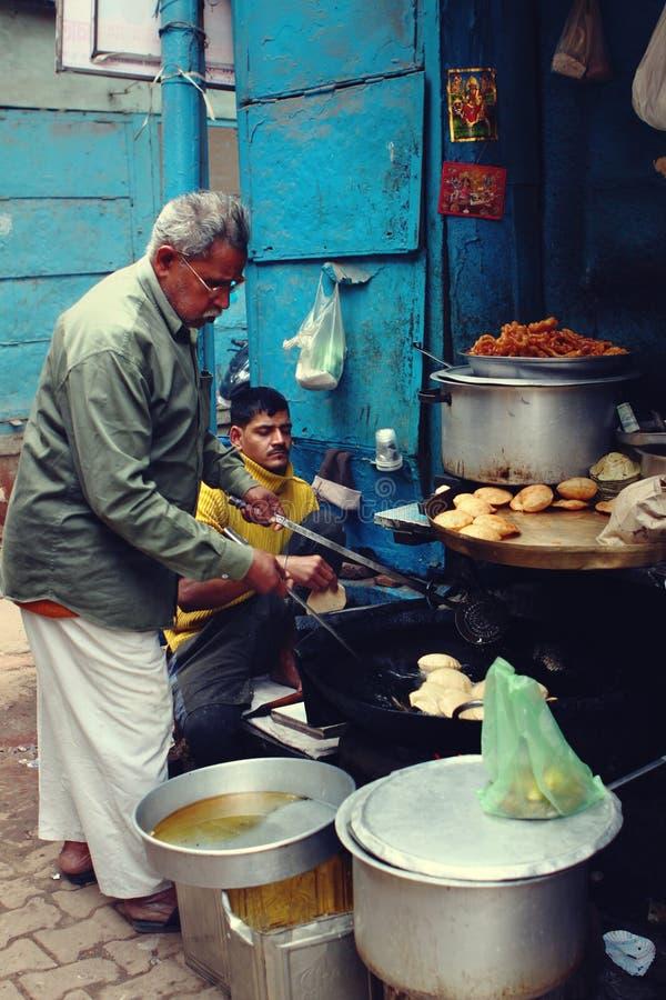 Os fabricantes tradicionais dos petiscos preparam o alimento famoso da rua em Varanasi, Índia fotografia de stock