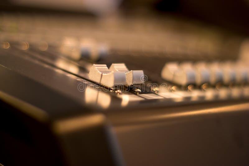 Os faders audio do misturador fecham-se acima com fundo borrado fotografia de stock royalty free